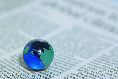 Glass globe over newspaper photo