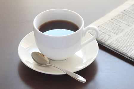 Cup of hot coffee  and newspaper photo