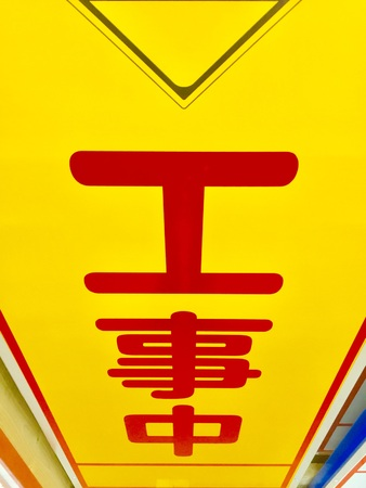 a japanese sign; under construction, men working road up