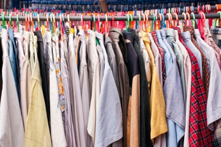 Een rek van tweedehandse shirts en t-shirts op een markt in Thailand