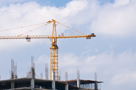 Construction crane against the blue sky and the houses under construction  Stock Photo - 15392735