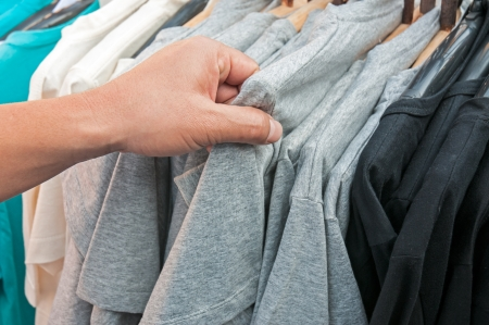 Close-up of a male customer looking for T-shirts in a fashion store  photo