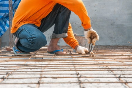 gridwork: Worker, rebar gridwork across a floor for strength  Stock Photo