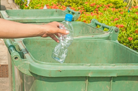 Male hand throwing empty plastic bottle into the trash  photo