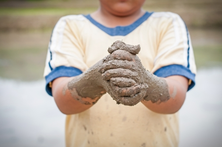 kids playing water: Boy hands with mud