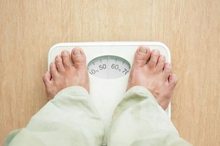 裸の足で体重計に立っている人 写真素材