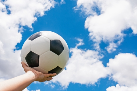 Classic soccer ball on hand with blue sky. photo