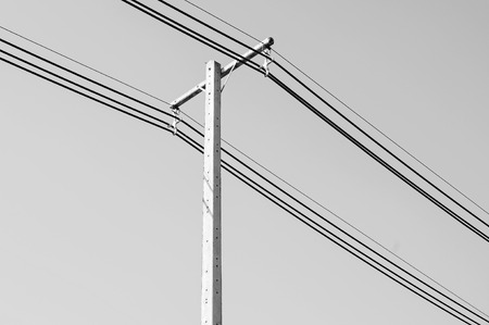 Black and white of electric power post with wire  photo
