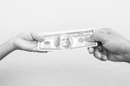 payoff: Black and white, Hand handing over money to another hand.