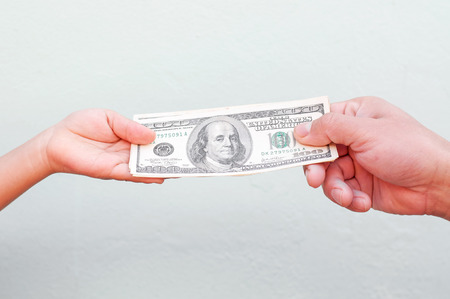 payoff: Hand handing over money to another hand. Stock Photo