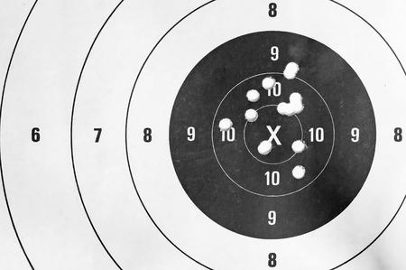 tiro al blanco: Blanco y negro, Primer plano de un blanco de tiro y diana de agujeros de bala Foto de archivo
