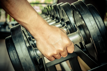 gym equipment: strong mans hand takes a heavy dumbbell in gym