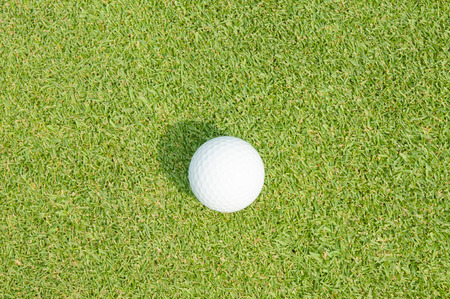 Golfball on grass infront of the green photo