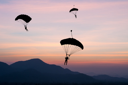 parachute jump: parachute at sunset silhouetted