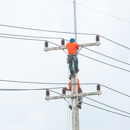 Electrician lineman repairman worker at climbing work on electric post power pole. photo