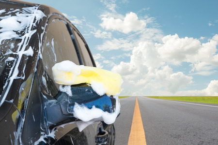 Sponge over the car for washing with blue sky. photo