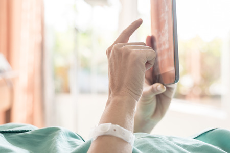 sick room: Mature female patient used tablet on bed in hospital