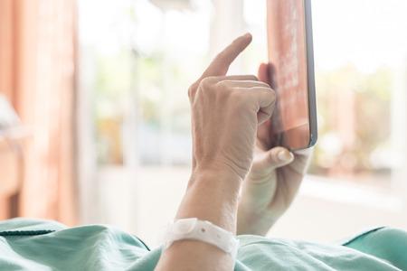 persona enferma: Paciente femenino maduro que usa la tableta en la cama en el hospital