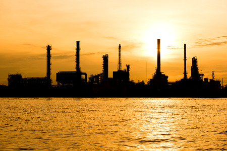 dramatic sunrise: silhouette oil indutry refinery  factory with dramatic sunrise Stock Photo