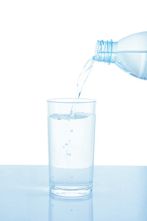 Pouring water from bottle into glass isolated on white background.