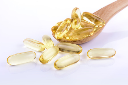 cod oil: Cod liver oil omega 3 gel capsules on white background Stock Photo