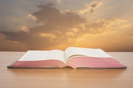 catholic: open bible with sunset sky