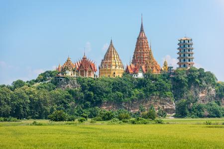 sua: Landscape of Thai temple  Wat Tham Sua  and rice field in Kanchanaburi, Thailand Stock Photo