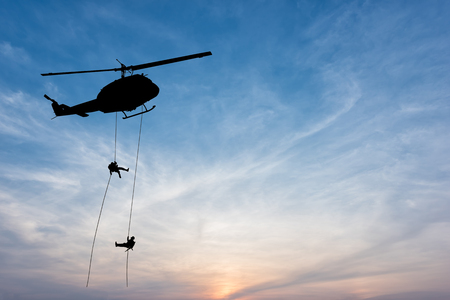 Silhouette of helicopter, soldiers rescue helicopter operations on sunset sky background. Stockfoto