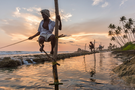 galle: KOGGALA, SRI LANKA - MARCH 22, 2016: Local men fishing in traditional way. traditional fishermen at the sunset near Galle in Sri Lanka.