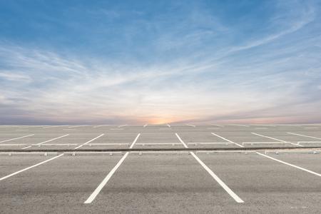 Leeg parkeerterrein op zonsondergangachtergrond