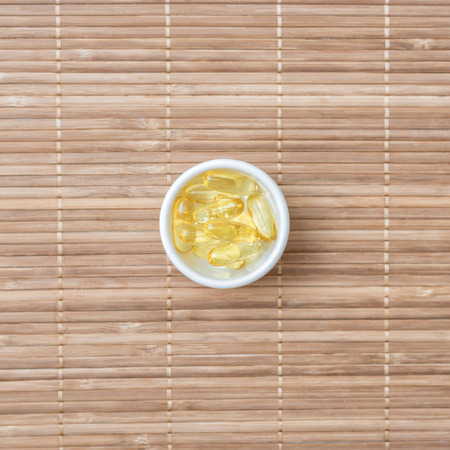 cod oil: Cod liver oil omega 3 gel capsules on bamboo mat�