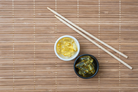 omega 3: Cod liver oil omega 3 gel capsules and chopsticks on bamboo mat