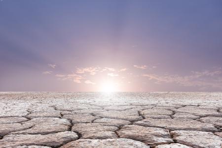 soil erosion: Soil drought cracked landscape on sunset sky background