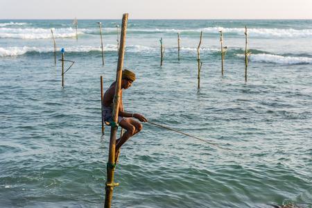 metier: KOGGALA, SRI LANKA - MARCH 22, 2016: Local men fishing in traditional way. traditional fishermen at the evening near Galle in Sri Lanka.