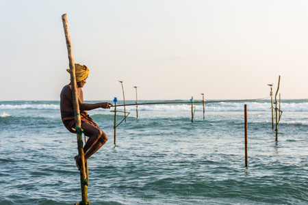 avocation: KOGGALA, SRI LANKA - MARCH 22, 2016: Local men fishing in traditional way. traditional fishermen at the evening near Galle in Sri Lanka.