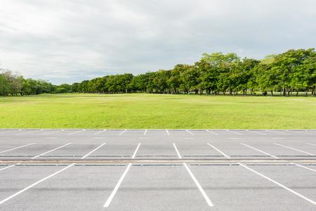 Empty parking lot against green lawn in city park Banco de Imagens