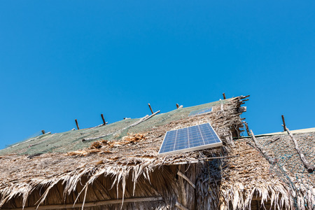 ecological adaptation: Solar panel on a roof of straw dry and the cloudless blue sky Stock Photo