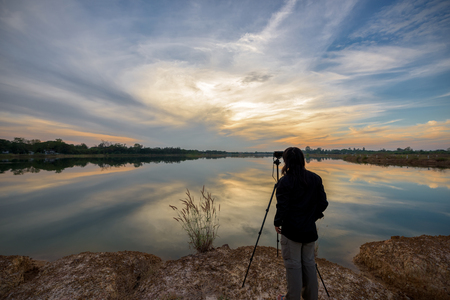 Photographer is taking a picture of landscape sunset. Stock Photo