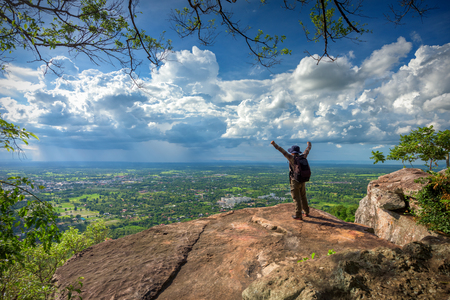 Young man traveler on cliff with beautiful landscape