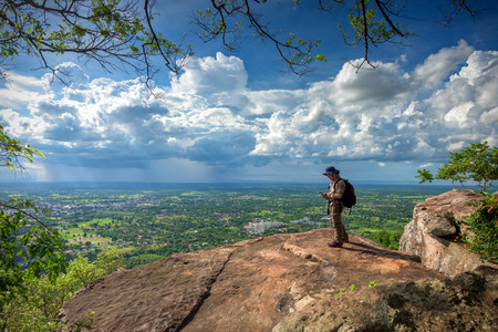 Man traveler is using digital phone on cliff with beautiful landscape Stock Photo