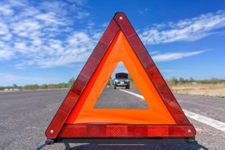 赤い緊急停止の標識と道路上の壊れた車