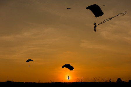 parachute jump: Silhouette of parachute and airplane on sunset background