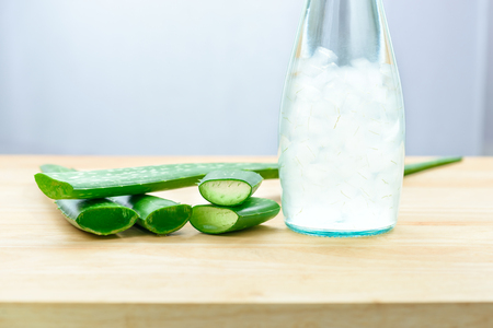 Aloe vera juice in bottle with fresh aloe vera leaves on wooden background