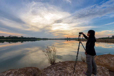pastime: Photographer is taking a picture of landscape sunset. Stock Photo