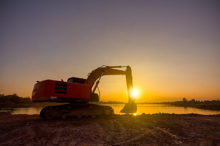 Backhoe was digging earthmoving work at construction site on sunset background Stock Photo - 80999698