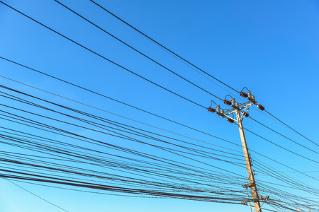 Electric pole and wires on blue sky Imagens