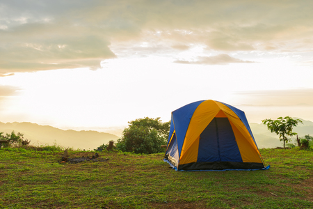 Tourist and tent in camp among meadow in the mountain at sunrise
