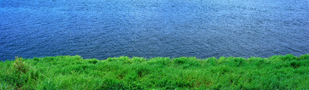 Panoramic grass and water background.