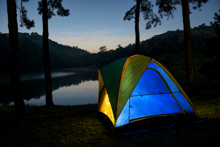 Illuminated blue camping tent at night Фото со стока