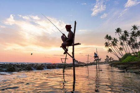 KOGGALA, SRI LANKA - MARCH 22, 2016: Local men fishing in traditional way. traditional fishermen at the evening near Galle in Sri Lanka.